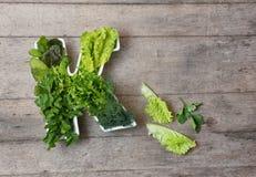 Vitamine K dans le concept de nourriture Plat sous forme de lettre K avec différents légumes verts feuillus frais, laitue, herbes photographie stock libre de droits