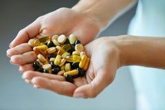 Vitamine und Ergänzungen Frau übergibt voll von den Medikations-Pillen lizenzfreie stockfotos