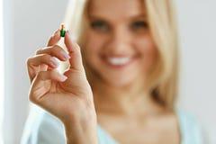 Vitamine und Lebensmittelergänzungen Schönheit mit Pille in der Hand lizenzfreie stockfotografie