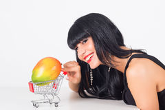 Vitamine. Young woman with mango in trolley Royalty Free Stock Image