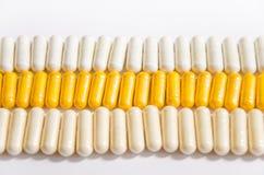 Vitaminen in capsules die op een rij liggen stock afbeeldingen