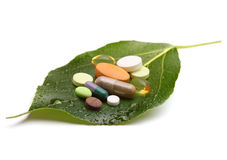 Vitaminen, tabletten en pillen op blad Stock Afbeelding