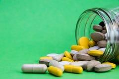 Vitaminendrugs uit dichtbij een geopende witte container die van de glaskruik worden verspreid en worden gemorst Behandeling met  royalty-vrije stock foto's