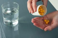 Vitaminer hälls in i handen Arkivfoton