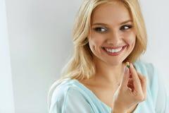 Vitaminer och mattillägg Härlig kvinna med preventivpilleren i hand Arkivfoto
