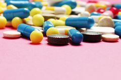Vitamines multicolores sur un fond rose image libre de droits