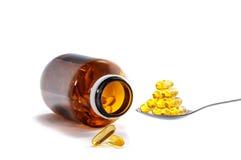 Vitaminflaska och sked Arkivbild