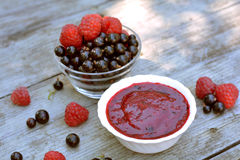 Vitaminic, red jam of home blackcurrant and red raspberry in white plate neat glass plate with full berries Royalty Free Stock Photo