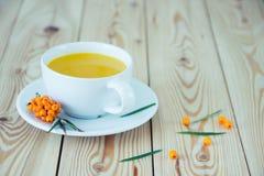 Vitaminic te med hav-buckthornen på trätabellen Arkivfoto