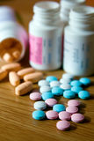 Vitamins. Closeup pink, white, blue and orange vitamins with bottles Stock Photo