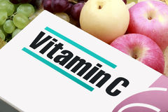 Vitamins. Vitamin C and its packaging with some fruits Stock Photography