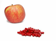 Vitamins. A stack of red vitamins pills and an apple isolated over white background-selective focus on the pills Stock Photography