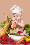 Vitamins. A little boy sitting in between vegetables Royalty Free Stock Photo