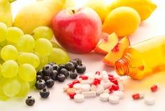 Vitamins. Vitamin pills with fresh fruits Stock Photo