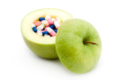 Vitamins. Concept - apple and pills inside it studio isolated Royalty Free Stock Photo