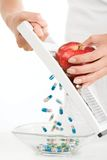 Vitamins. Close-up of vitamins and pills spilling into bowl while female grating red apple Royalty Free Stock Photos