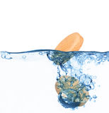 Vitamins fall into the water on a white Royalty Free Stock Photo
