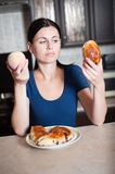 Vitamins or farinaceous food. Young woman chooses between a peach and pie. Care about health Stock Images