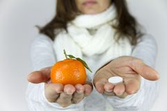 Vitamins from fruit or drugs? A sick young woman with a scarf on her neck shows a mandarin in her right hand and an aspirin on her stock photography