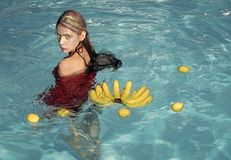 Vitamins and health. Summer vacation and travel to ocean. Vitamin in banana at girl sitting near water. Woman relax in. Spa pool. woman with tropical fruit in royalty free stock image