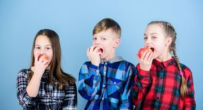 Vitamins are important for children. Little children biting red vitamin apples. Small children enjoy eating apples full. Of vitamins. Natural vitamins helping stock photography