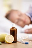 Vitamins medicines for flu woman in background. Vitamins, medicines and lemons in front, woman caught cold sleeping in background Royalty Free Stock Photo
