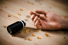 Vitamins overdose. Concept - passive hand on floor and spillage pills Royalty Free Stock Images