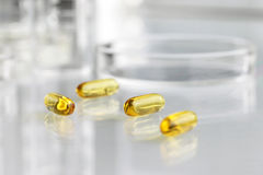 Vitamins pills omega 3 supplements with petri dish. Close up stock photography