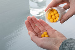 Vitamins are poured into hand Royalty Free Stock Photography
