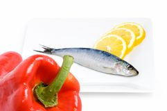Vitamins and sardine. Two photos put together, one with the paprika, and the other one with the sardine and the lemon on a plate Stock Photos