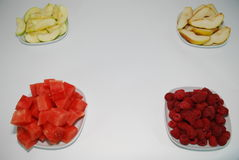 Vitamins. Sliced ​​pears, apples, watermelon and ripe juicy raspberries, lie on white plates.They beckon to their beauty and usefulness .All plates are stock images