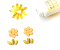 Vitamins supplements for health. A concept still life image of some assorted vitamin pills and capsules making a happy picture of healthily growing plants in the Royalty Free Stock Photos