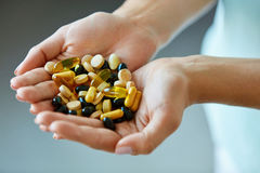 Vitamins And Supplements. Woman Hands Full Of Medication Pills Royalty Free Stock Photos