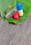 Vitamins, tablets and pills on green leaf Stock Photos