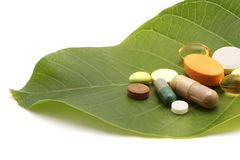 Vitamins, tablets and pills on leaf Royalty Free Stock Photos