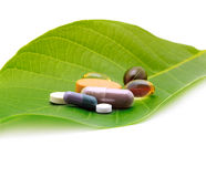 Vitamins, tablets and pills on leaf Stock Photo