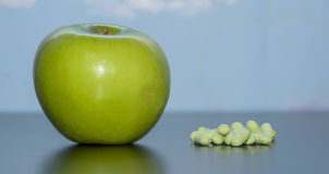 Vitamins to choose an apple or pills Stock Photography