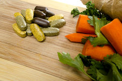 Vitamins and Vegis. Vitamins on a cutting board with vegetables Stock Images