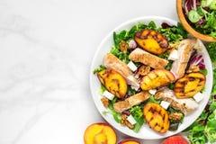 Vitaminsallad med grillad höna och persika, fetaost och valnötter i en platta sund mat Top beskådar arkivbild