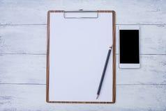 Vitbok på träskrivplattan med den nya vita smartphonen Arkivfoto