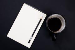 Vitboknotepad och en kopp kaffe på svart svart tavlabaksida Royaltyfria Foton