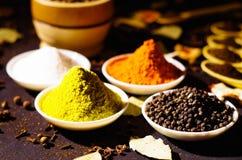 Vitbunkar fördelade ut med olika färgrika kryddor inom, den härliga lantliga inställningen, kryddan och växt- begrepp Arkivbilder