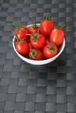 Vitbunke som fylls med lilla nya tomater på grå färgbakgrund Royaltyfria Bilder