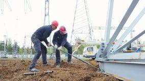 Vite di torsione dei lavoratori per installare supporto su terra stock footage