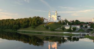 Vitebsk, Belarus. Assumption Cathedral Church in upper town on Uspensky Mount Hill and Dvina river in summer evening. Sunset time. Zoom, Zoom In stock video footage