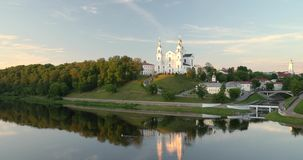 Vitebsk, Belarus. Assumption Cathedral Church in upper town on Uspensky Mount Hill and Dvina river in summer evening. Sunset time. Zoom, Zoom Out stock video footage