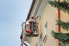Woman in bucket at height painting facade of building in Vitebsk. Vitebsk, Belarus - August 05, 2013: Woman in bucket at height painting facade of building in stock illustration