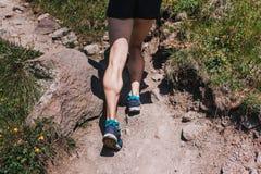 Vitelas musculares de um atleta novo que corre acima um trajeto da montanha, u imagem de stock