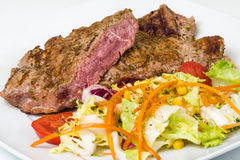 Vitello della fetta raro con insalata sul piatto Fotografia Stock