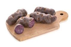 Vitelotte,在堆的紫色土豆在一个木切板 图库摄影
